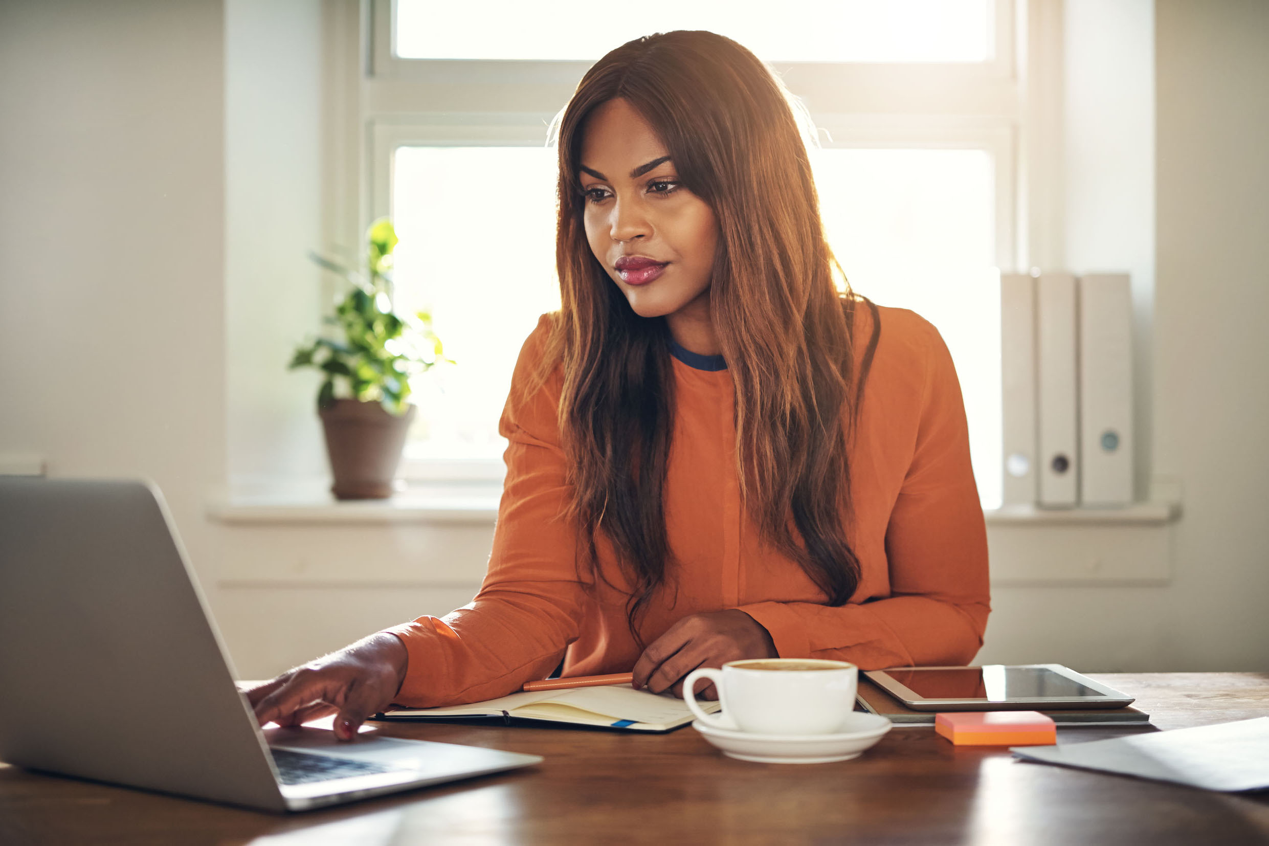Woman on her laptop at home with a cup of coffee.