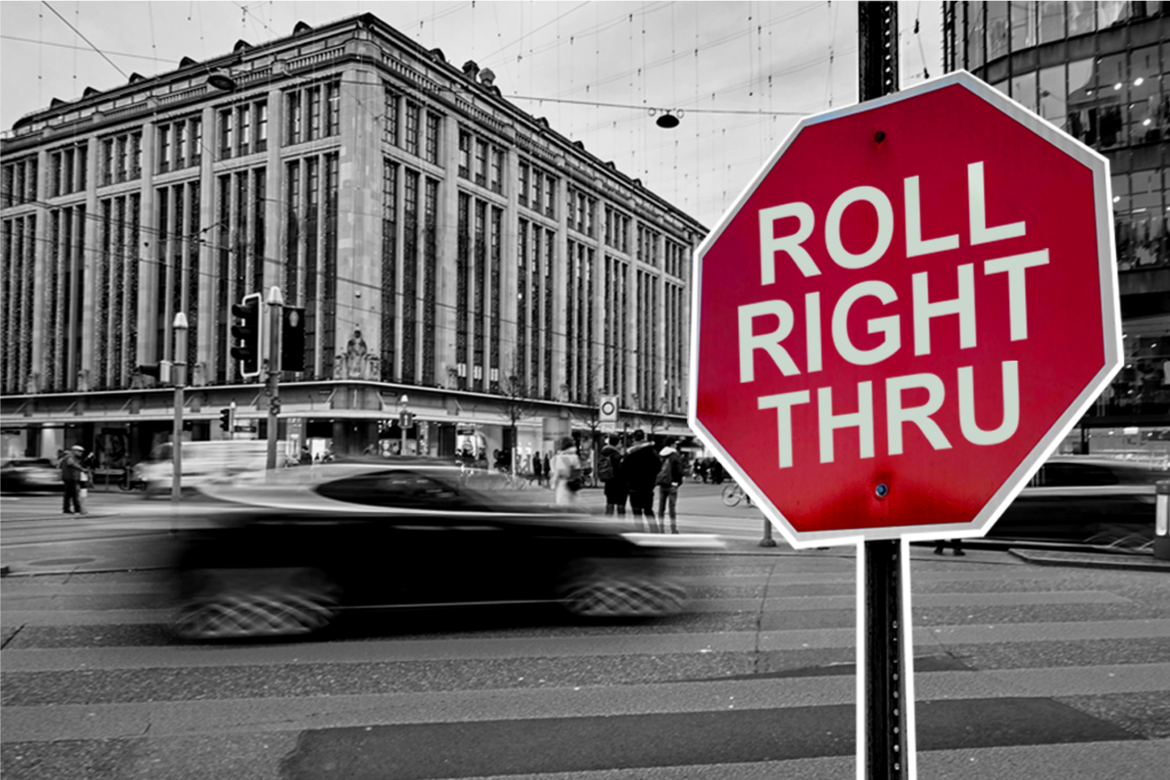 Black and white city photo featuring red stop sign reading