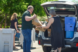 Shred Day attendees removing bags of shred material from the trunk of an SUV.