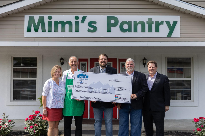 Image description: Dennis Curtin accepts his Good Neighbor Award check outside the Mimi's Pantry building.