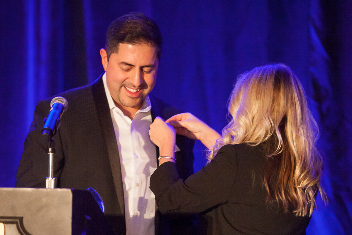 Photo: Majid Ghavami receiving an award on stage at KCRAR's 2019 Holiday Party.