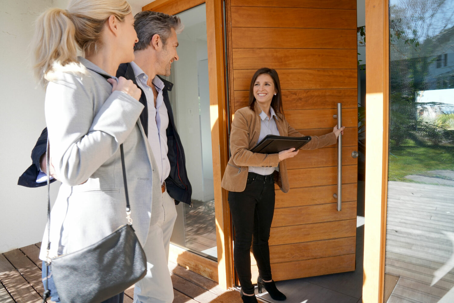 Image description: Real estate agent inviting couple to enter house for visit.