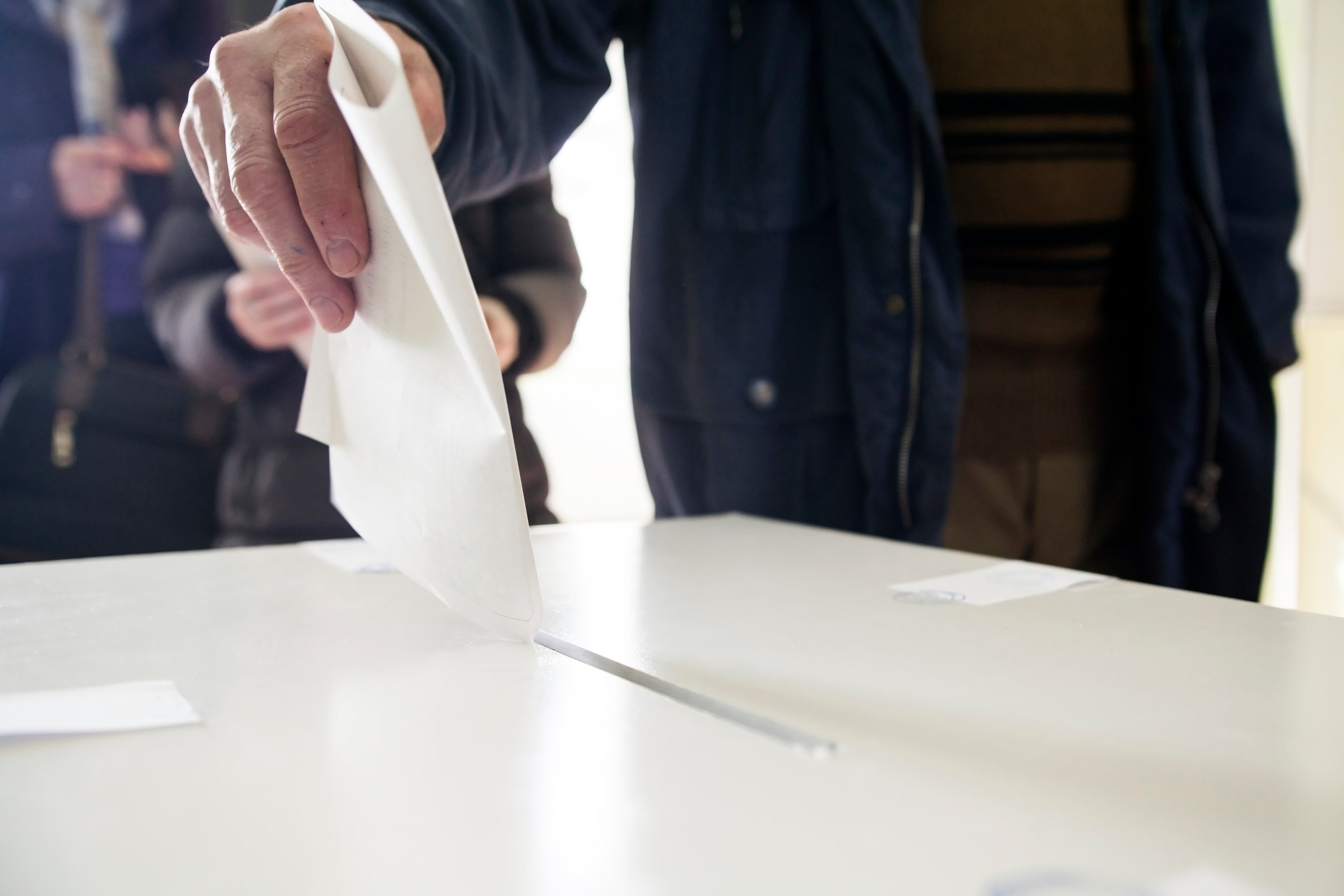 Image description: Hand of a person casting a ballot at a polling station during voting.