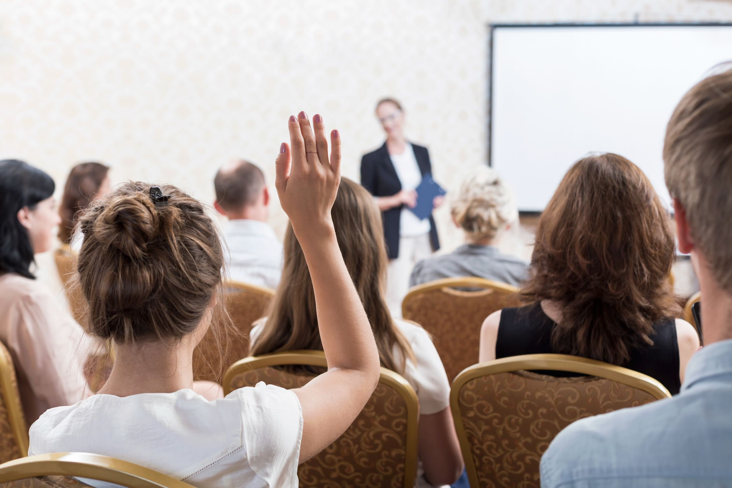 Photo description: listener raising hand to ask question during seminar.