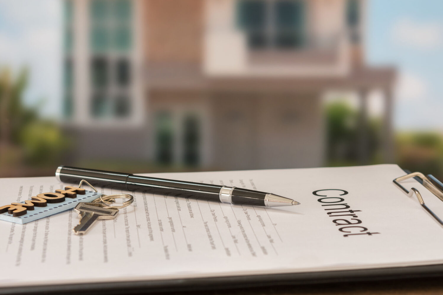 Image description: Closeup pen on contract document with house in background.