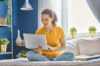 Image description: Person using laptop at home to search for down payment assistance programs
