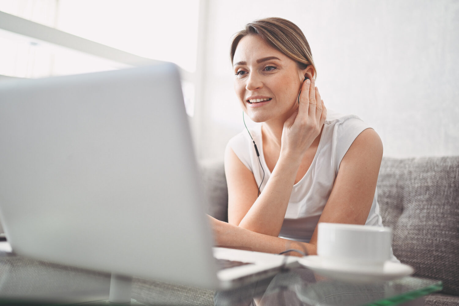 Image description: Person watching virtual townhall on her laptop at home.