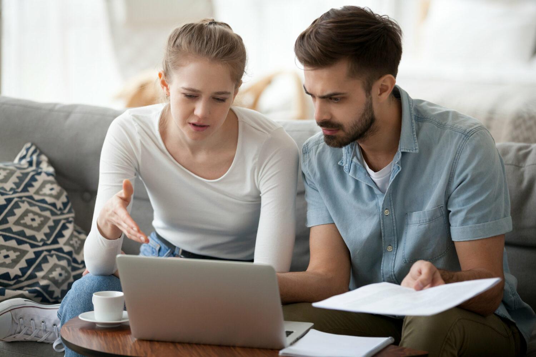 Image description: Two millennials discuss their finances in their home.