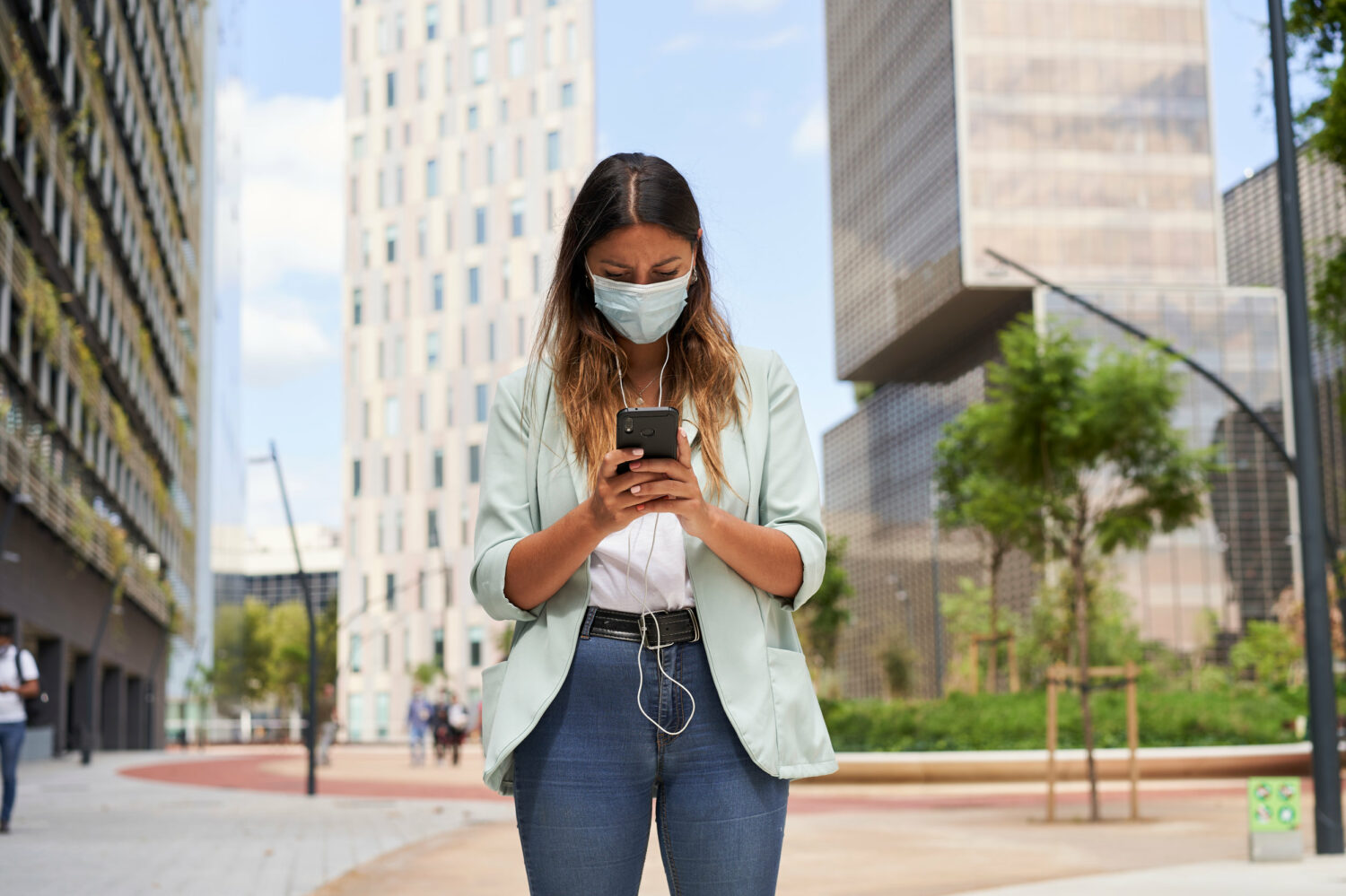 Image description: Young woman using the Noonlight safety app outdoors in the city.