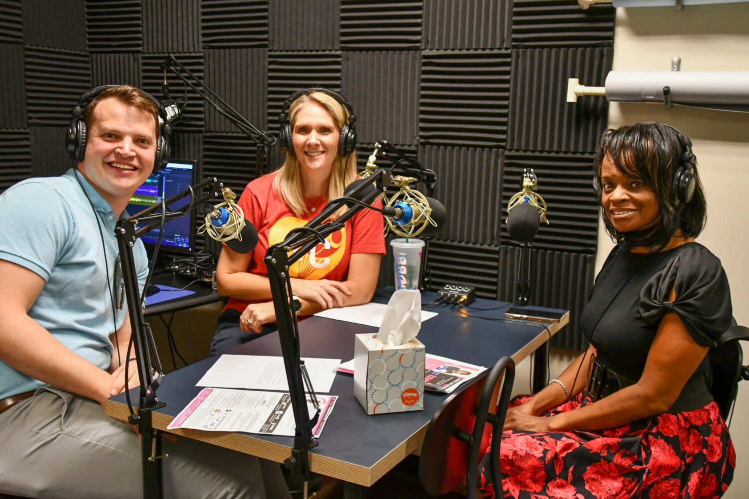 Image description: Kansas City RealTalk hosts Bobbi and Alex sit across the mics from safety expert Tracey Hawkins as they record a 2019 episode.