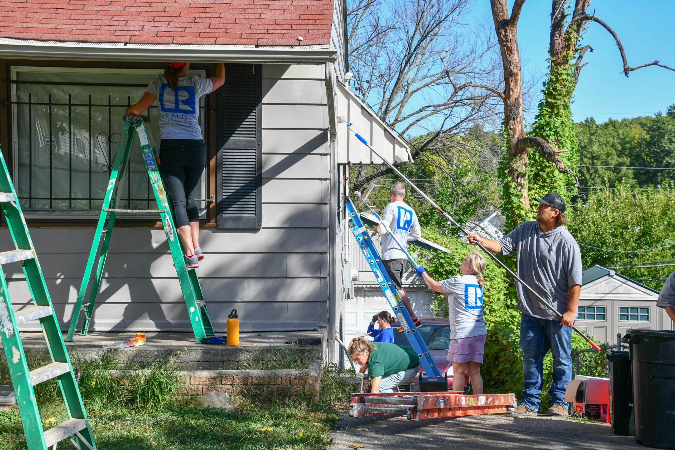 Image description: Realtors paint a home at Rock the Block.